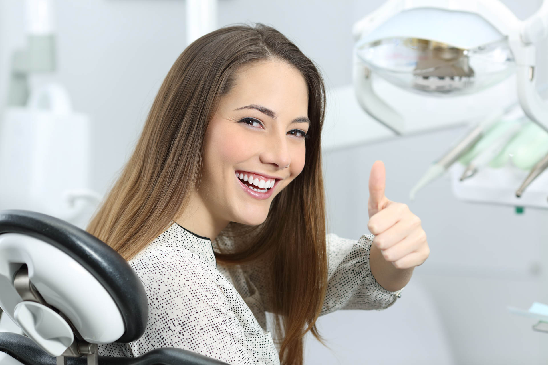 Patient satisfied after dental treatment with medical equipment in the background